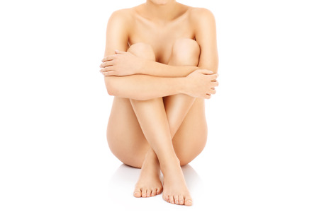 naked woman sitting: Beautiful young nude woman over white background Stock Photo