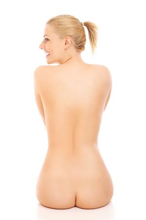 mujer desnuda sentada: Joven mujer desnuda sentada en la mesa sobre fondo blanco