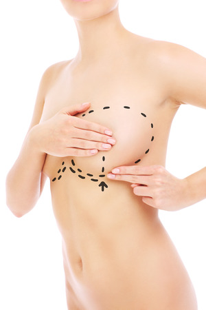 Woman and preparations for breast surgery over white background