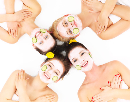 A picture of four friends enjoying their time in spa with facial masks over white background photo