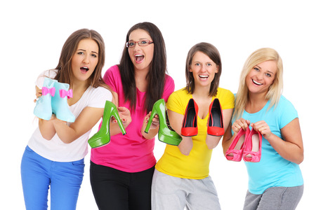 Four young womans holding color shoes over white background photo