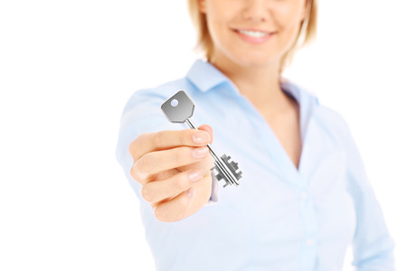 Young woman giving key over white background photo