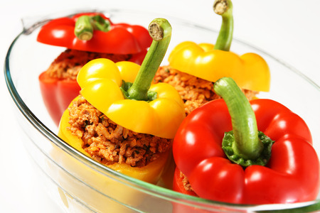 heatproof: A picture of an unbaked yellow and red stuffed peppers served in a heatproof glass Stock Photo