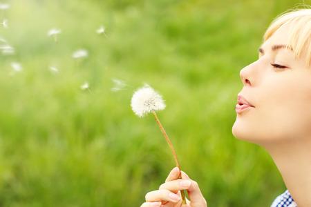 緑の背景にタンポポを吹く女性の画像