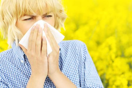 nariz: Un retrato de una mujer de estornudar en un campo amarillo de las flores Foto de archivo