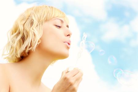 burbujas de jabon: Una imagen de una hermosa mujer soplando burbujas de jabón en el cielo