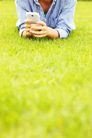 A picture of a woman with cellphone lying on grass photo