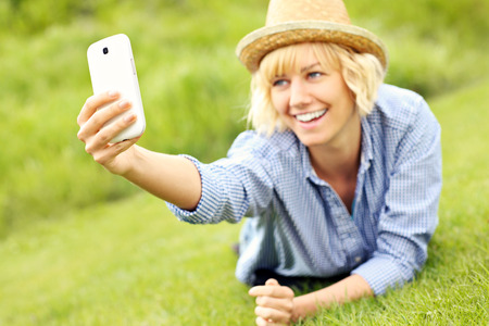 A picture of a woman lying on grass and taking pictures with cellphone photo