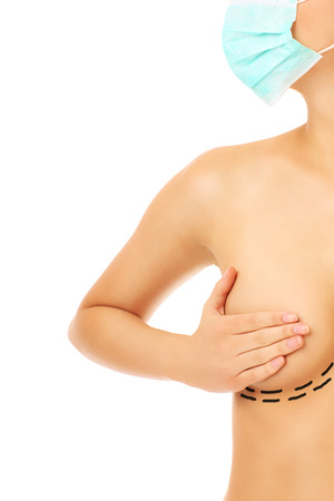 A picture of a woman with a surgical mask showing her breast over white background photo