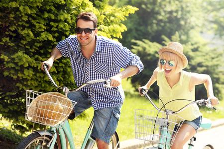andando en bicicleta: Una imagen de una pareja feliz de pasar el tiempo libre en bicicleta en la ciudad Foto de archivo