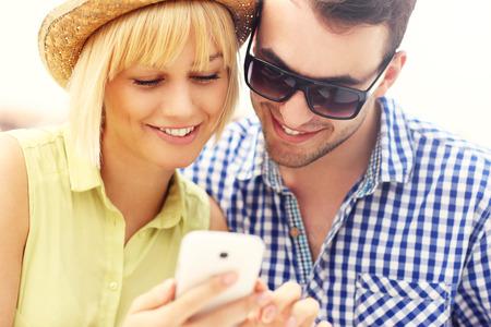 A picture of a young couple using a phone Фото со стока