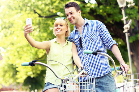 A picture of a happy couple taking pictures of themselves on a bike photo