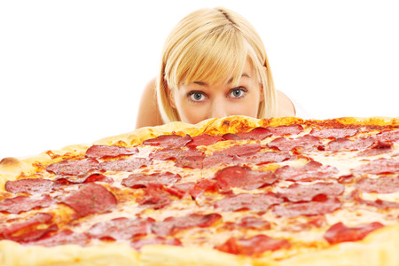 A picture of a curious woman looking at pizza over white background photo