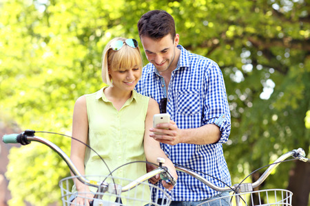 A picture of a young couple on bikes with a cellphone photo