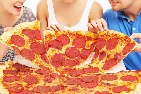 eating pizza: A picture of a group of friends with pizza
