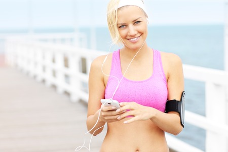 Young woman with phone listening music on pier photo