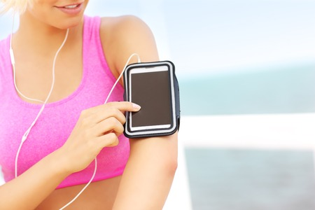 armband: Primo piano della donna di misura che toccano telefono collocato in fascia da braccio