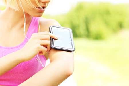 armband: Close up of phone over fit running woman in the park Stock Photo