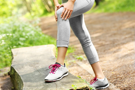 foot pain: A picture of a jogger having problems with knee in the forest Stock Photo
