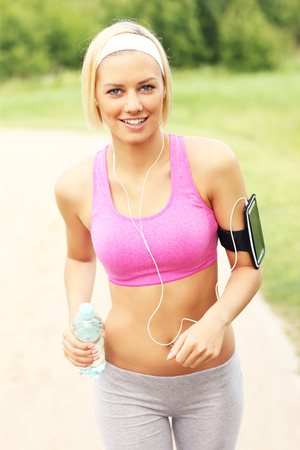 sports bra: A picture of a woman jogging in the park with a bottle of water