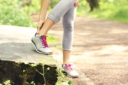A picture of a jogger having problems with ankle in the forest photo