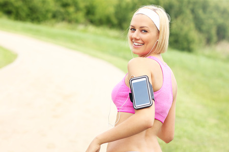 A picture of a jogger with smartphone in the park photo