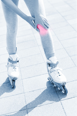 blading: A picture of a woman having problem with knee while roller blading