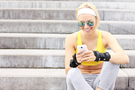 rollerblading: A picture of a happy woman using cellphone on concrete stairs