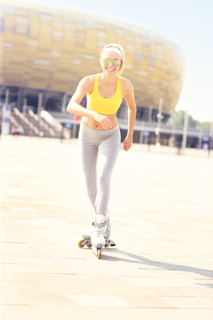 blader: A picture of a happy roller blader skating in front of the Amber Stadium in Gdansk