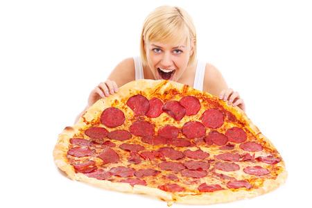 Een foto van een gelukkige vrouw het eten van een grote pizza op een witte achtergrond Stockfoto