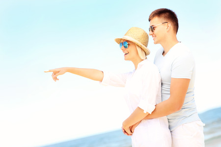 A picture of a joyful couple pointing to the sky at the beach photo