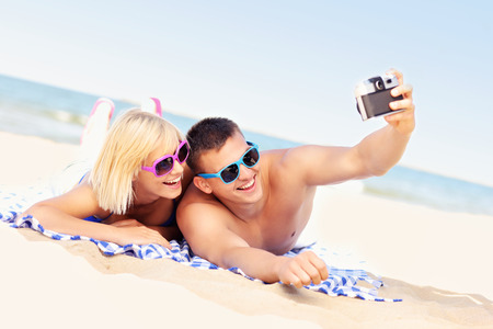 personas tomando agua: Una imagen de una joven pareja haciendo fotos en la playa