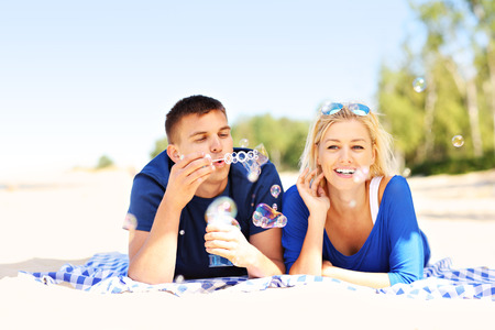 A picture of a young couple blowing bubbles at the beach photo