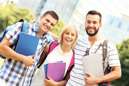 A picture of a group of students standing in front of modern buildings photo