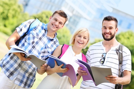 A picture of a group of students standing in the park in front of modern buildings photo