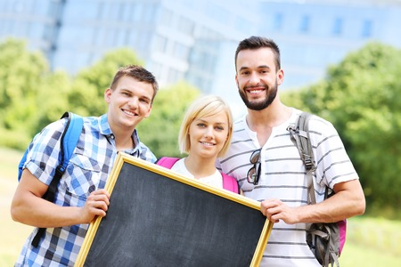A picture of a group of students standing in the park and holding a blackboard photo