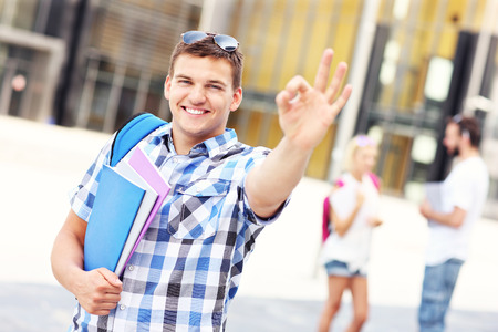 sign university: A picture of a young student showing ok sign in the campus