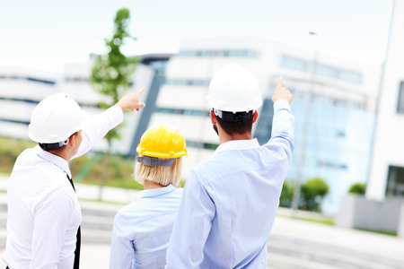 engeneer: A picture of a group of architects on site pointing at modern buildings