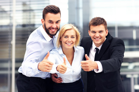 A picture of a cheerful business team outside modern building photo