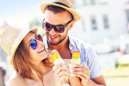 市内のアイス クリームを食べる素敵なカップルの写真