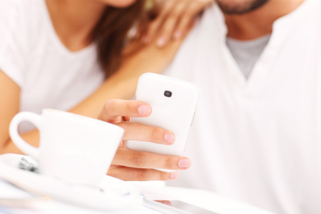 A closeup of hands and smartphone in a cafe photo