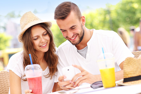 A picture of a happy couple using smartphone in a cafe Stock Photo