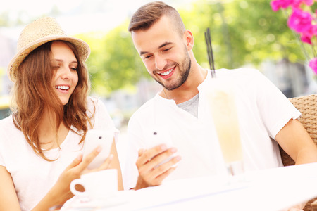 A picture of a happy couple with their smartphones in a cafe photo