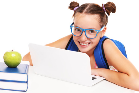 apple computer: A picture of a smart schoolgirl with laptop and books over white background