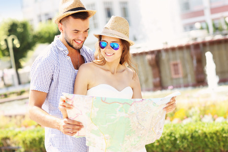 A picture of young couple of tourists standing with a map in the park photo