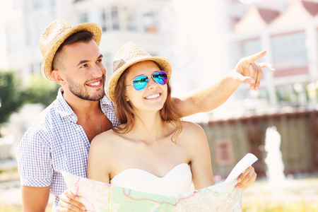 A picture of young couple of tourists standing with a map in Sopot photo