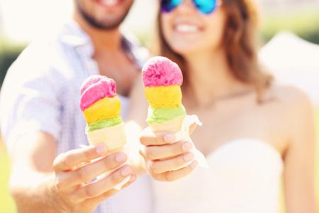 hombre comiendo: Una imagen de una pareja feliz que muestra los conos de helado Foto de archivo