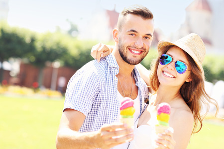 A picture of a joyful couple eating ice-cream cones in the park