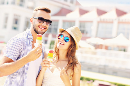 pareja comiendo: Una imagen de una pareja alegre comiendo conos de helado en la ciudad Foto de archivo