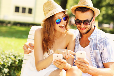 A picture of a young couple sitting on a bench with smartphones